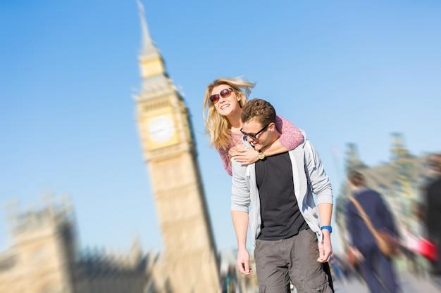 Gelukkig jong paar dat van een op de rug rit in londen geniet