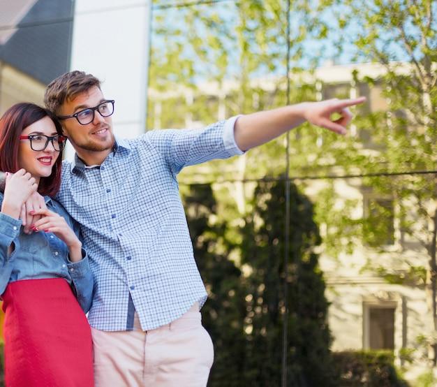 Gelukkig jong paar dat zich bij straat van stad bevindt en op de heldere zonnige dag lacht
