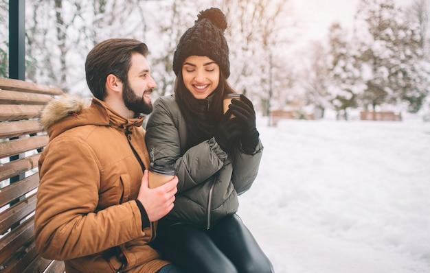 Gelukkig jong paar in de winter die een koffie in een sneeuwlandschap neemt
