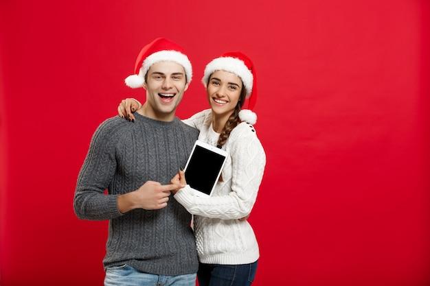 Gelukkig jong paar in kerstmissweaters die digitale tablet houden.