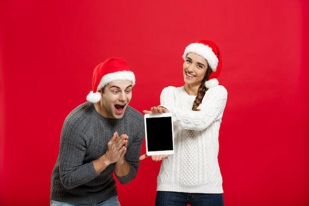 Gelukkig jong paar in kerstmissweaters die iets in digitale tablet verrassen.