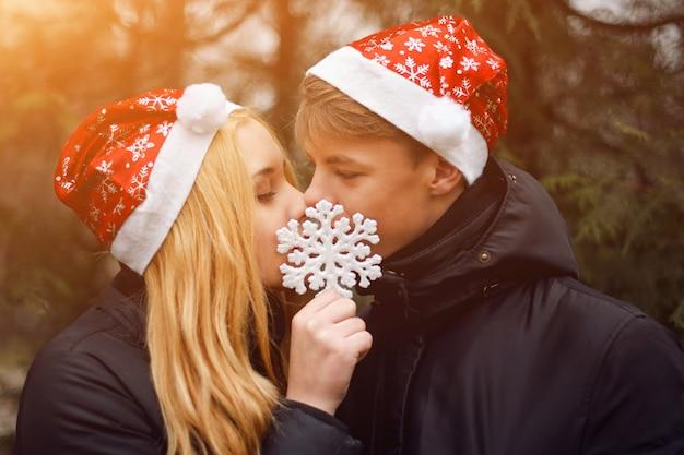 Gelukkig jong paar in liefde die kerstmanhoeden dragen die en een grote sneeuwvlok kussen houden
