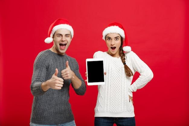 Gelukkig jong paar in sweaters die kerstmis met het spelen en het dansen vieren.