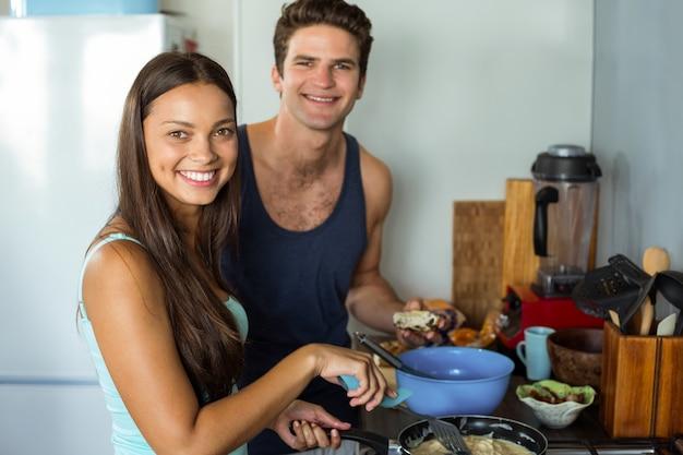 Gelukkig jong paar kokend voedsel in keuken