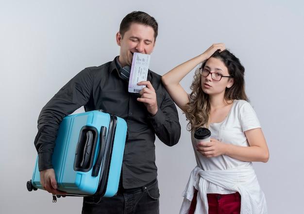 Gelukkig jong paar toeristenman en vrouwenholding koffer en vliegtickets die zich over witte muur bevinden