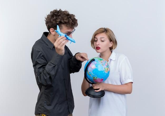 Gelukkig jong paar van toeristenman en vrouwenholding bol en stuk speelgoed vliegtuig die zich over witte muur verenigen