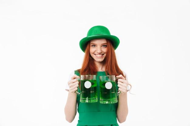 Gelukkig jong roodharige meisje met groene hoed, vieren st patricks's day geïsoleerd over witte muur, bier drinken