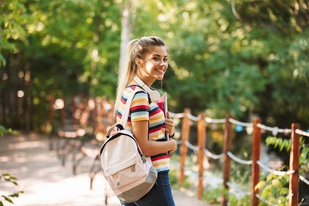 Gelukkig jong schattig meisje student wandelen in park met rugzak.