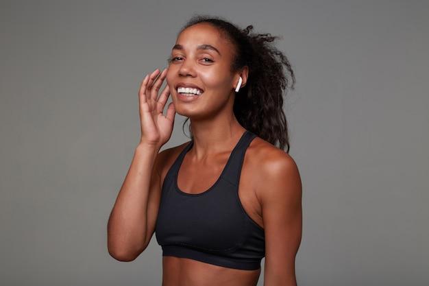 Gelukkig jong slank krullend langharige vrouw in atletische slijtage hand opsteken naar haar gezicht en vrolijk lacht, staande met koptelefoon in haar oren