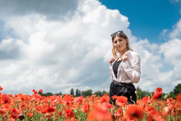 Gelukkig jong slank meisje lopen op het gebied van rode papavers, tijd doorbrengen, zomer