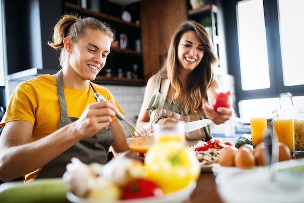 Gelukkig jong stel dat plezier heeft in de moderne keuken tijdens het bereiden van vers voedsel