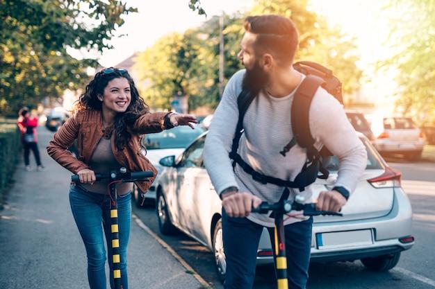 Gelukkig jong stel dat samen geniet tijdens het rijden op elektrische scooters in het stadspark.