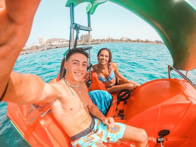 Gelukkig jong stel dat selfie-foto's maakt en samen van de zomervakantie geniet terwijl ze in de boot zitten. paar in korte broek en bikini genieten van boottocht op zee tijdens zomervakantie