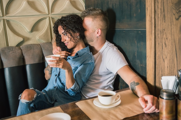 Gelukkig jong stel drinkt koffie en lacht terwijl ze in het café zitten. ik houd van jou. romantische mooie jonge liefdevolle man en vrouw verliefd. meisje en vriendje samen. kaukasische modellen. levensstijl