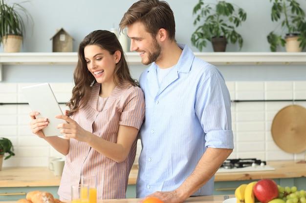 Gelukkig jong stel in pyjama kijken naar online inhoud in een tablet en glimlachen tijdens het koken in de keuken thuis.