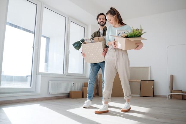Gelukkig jong stel met dozen die verhuizen in een nieuw appartement, een nieuw huis en een verhuisconcept.