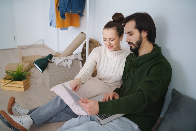 Gelukkig jong stel met laptop en dozen die verhuizen in een nieuw appartement, een nieuw huis en een verhuisconcept.