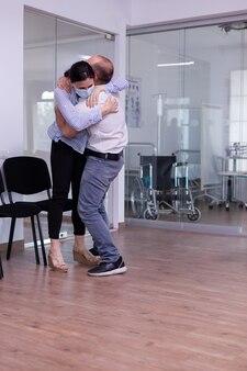 Gelukkig jong stel na goed ontvangen van een arts die een gezichtsmasker draagt in de wachtruimte van het ziekenhuis, terwijl ze elkaar omhelzen