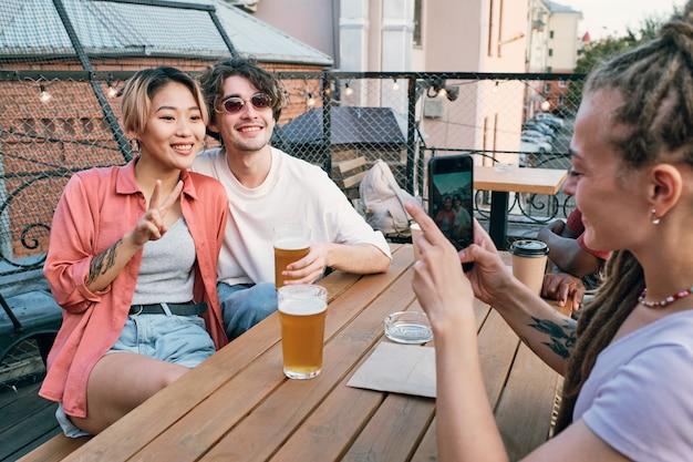 Gelukkig jong stel poseren voor hun vriend met smartphone