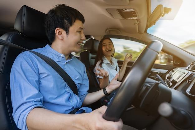 Gelukkig jong stel praat tijdens het autorijden