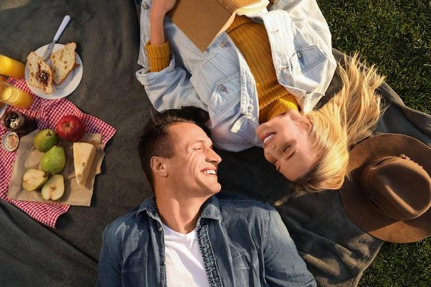 Gelukkig jong stel rust terwijl ze buiten picknicken op een zonnige dag, bovenaanzicht