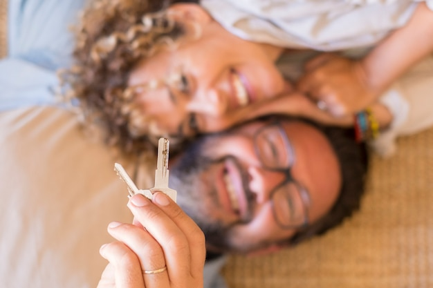 Gelukkig jong stel toont nieuwe eigen huissleutels opgewonden om samen te verhuizen, glimlachend liefhebbende volwassen man en vrouw dolgelukkige eerste keer dat kopers verhuizen huur gedeeld appartement