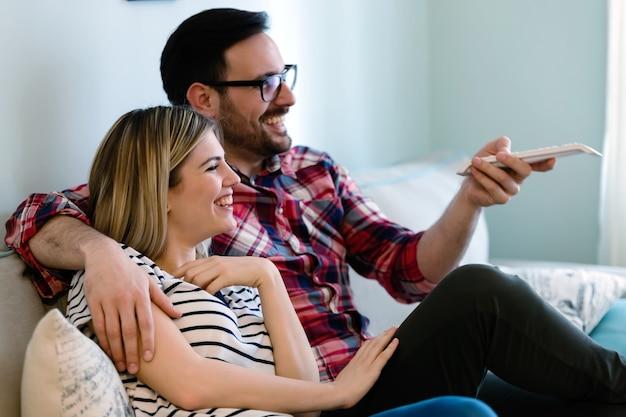 Gelukkig jong stel tv kijken in hun huis