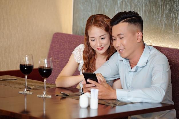 Gelukkig jong stel zit aan cafétafel, drinkt wijn en leest interessante berichten op sociale media of kijkt naar nieuwe video van beroemde blogger