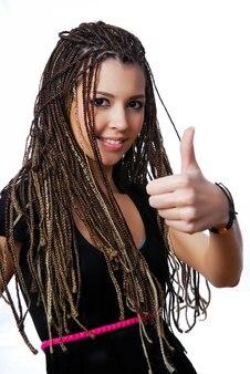 Gelukkig jong tienermeisje met schoonheidsdreadlocks die thumbsup-teken tonen