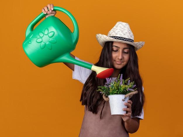 Gelukkig jong tuinman meisje in schort en zomerhoed met gieter en potplant drenken plant met glimlach op gezicht staande over oranje muur