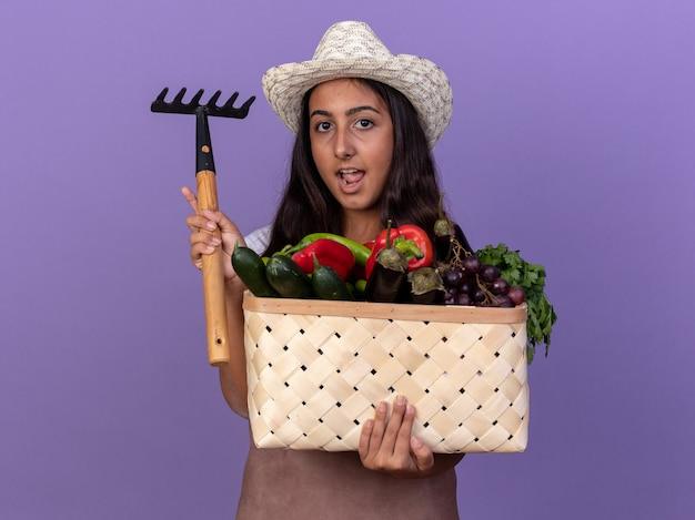 Gelukkig jong tuinman meisje in schort en zomerhoed met krat vol groenten en minihark met glimlach op gezicht staande over paarse muur