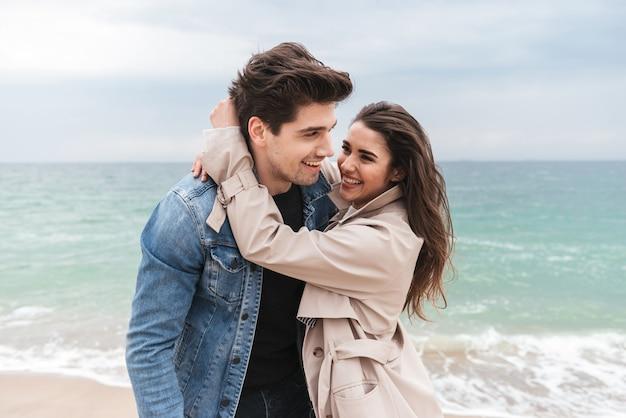 Gelukkig jong verliefd stel met herfstjassen die samen tijd doorbrengen aan de kust, knuffelen