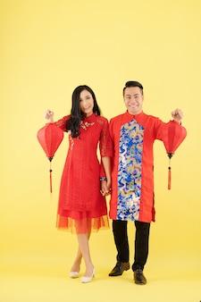 Gelukkig jong vietnamees koppel in traditionele jurken hand in hand en tonen zijden lantaarns voor tet-viering