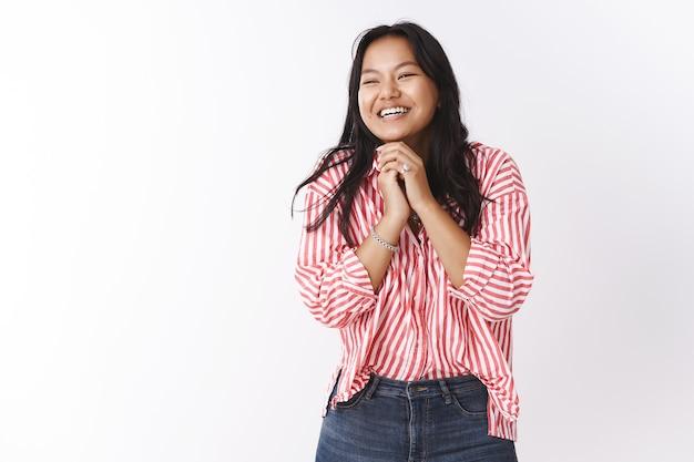 Gelukkig jong vietnamees meisje op wolk negen van vreugde en opgetogen dol op geweldig valentijnscadeau handpalmen tegen elkaar drukkend glimlachend blij en blij kijkend links dromerig, gevuld met geluk