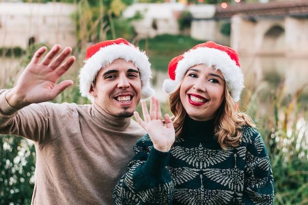 Gelukkig jong volwassen stel zwaaien naar camera tijdens videogesprek via laptop op eerste kerstdag. achtergrond voor video-oproep.