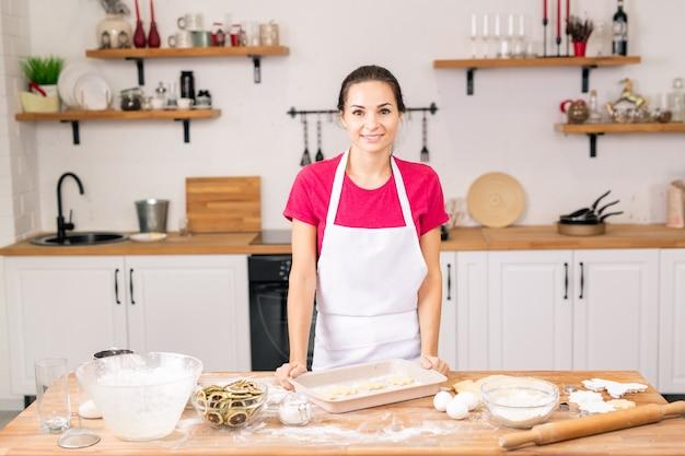 Gelukkig jong wijfje dat zich bij lijst in de keuken bevindt terwijl zij koekjes met citroen voor haar familie gaat maken