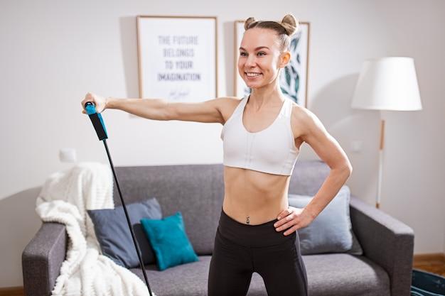 Gelukkig jong wijfje in sportkleding die hand op taille houden en glimlachen tijdens het uitrekken van elastisch koord tijdens fitnesstraining thuis