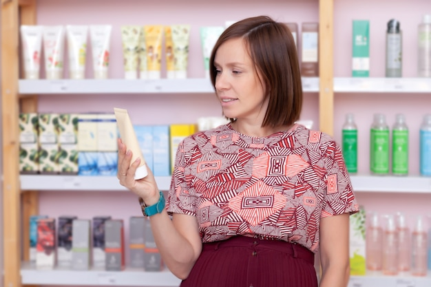 Gelukkig jong zwanger kaukasisch vrouwenbrunette kiest het droge lichaam van het huidverzorgingsproduct, gezicht, oogleden. koper tevreden met service in cosmetica winkel, parfums, medische goederen. zwangerschap en winkelen
