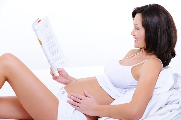 Gelukkig jong zwanger vrouwelijk lezingsmagazine
