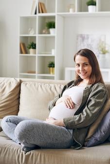 Gelukkig jong zwanger wijfje in vrijetijdskledingzitting onder kussens op laag in thuisomgeving