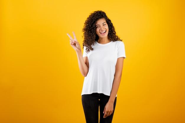 Gelukkig jong zwart meisje dat vredesgebaar toont dat over geel wordt geïsoleerd