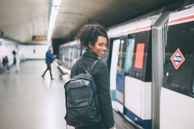 Gelukkig jong zwarte binnen het ondergrondse station dat op de trein wacht