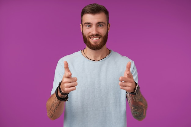 Gelukkig jonge aantrekkelijke brunette man met baard vrolijk en glimlachend, handen met duimen opheffen en zijn aangename emoties tonen, geïsoleerd op paars