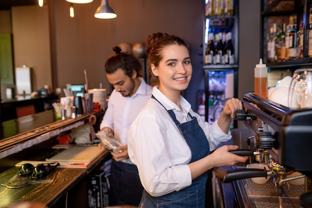 Gelukkig jonge aantrekkelijke serveerster van café of restaurant cappuccino bereiden door koffiemachine met collega op achtergrond
