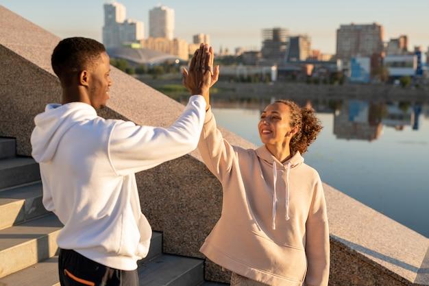 Gelukkig jonge actieve vrouwelijke en afrikaanse sportman in hoodies die elkaar high five geven na de training terwijl ze tegen de rivier staan