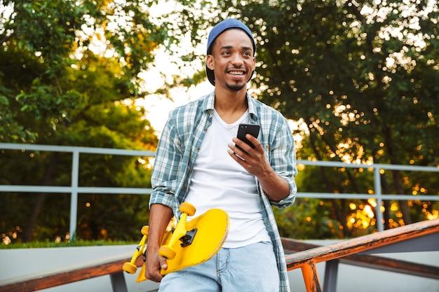 Gelukkig jonge afrikaanse man met skateboard