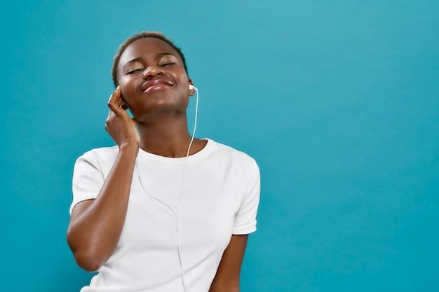 Gelukkig jonge afrikaanse vrouw luisteren muziek met gesloten ogen.