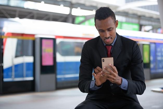 Gelukkig jonge afrikaanse zakenman met behulp van telefoon op het treinstation