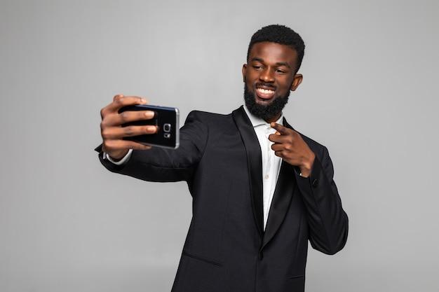 Gelukkig jonge afrikaanse zakenman selfie te nemen gericht op camera