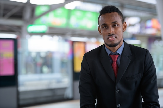 Gelukkig jonge afrikaanse zakenman te wachten op het treinstation